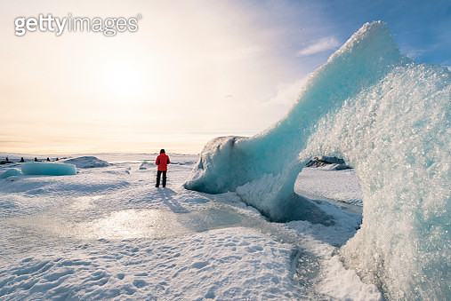 Fjallsarlon glacier lagoon, East Iceland, Iceland. Man with red coat admiring the view of the frozen lagoon in winter (MR). - gettyimageskorea