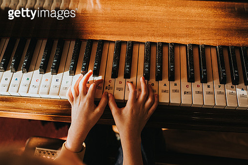 Child learning Piano, with Stickers on the keys for Guidance - gettyimageskorea