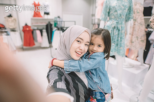 an asian malay young woman shopping in a boutique shop with her daughter - gettyimageskorea