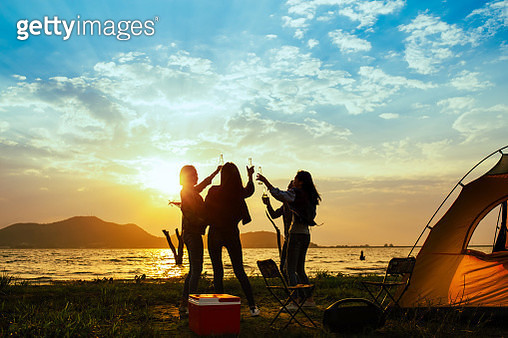 Friends Partying While Camping At Beach Against Sky During Sunset - gettyimageskorea