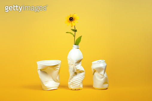 White plastic containers for recycling (cup, bottle, can) repurposed as vases with yellow coneflower on a yellow background. - gettyimageskorea
