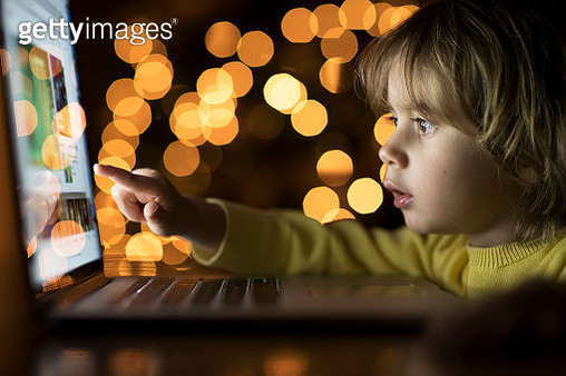 2 year old boy looking a laptop in the dark - gettyimageskorea
