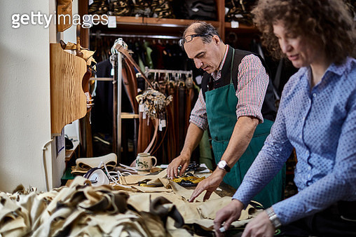 Tailor and his wife working on samples for Bavarian lederhosen - gettyimageskorea