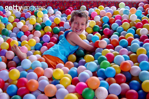 Boy playing in pool ball and smiling - gettyimageskorea