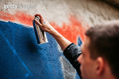 Man painting graffiti on wall - gettyimageskorea