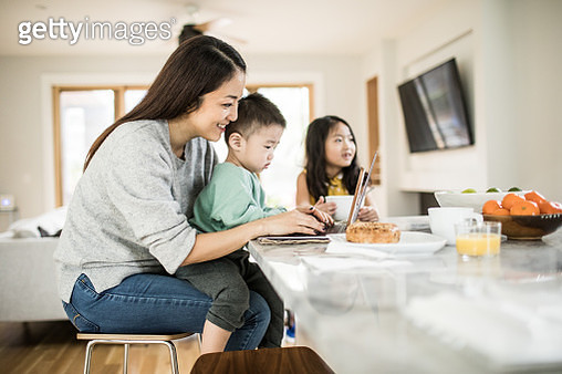 Mother multi-tasking with young children in kitchen table - gettyimageskorea