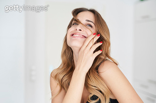 Happy young woman playing with her hair - gettyimageskorea