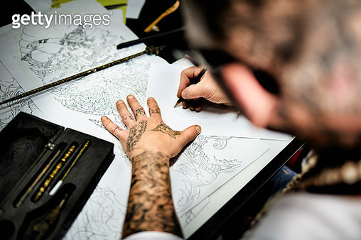 Close-up of tattooist working on draft at desk in his studio - gettyimageskorea