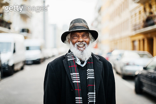 A portrait of a mature man with a beard standing in the street, smiling. - gettyimageskorea