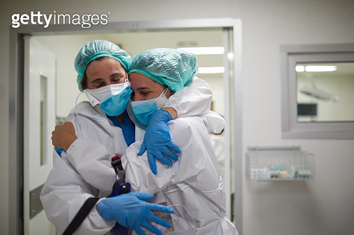 Two healthcare workers hug in celebration of a successful surgery procedure - gettyimageskorea