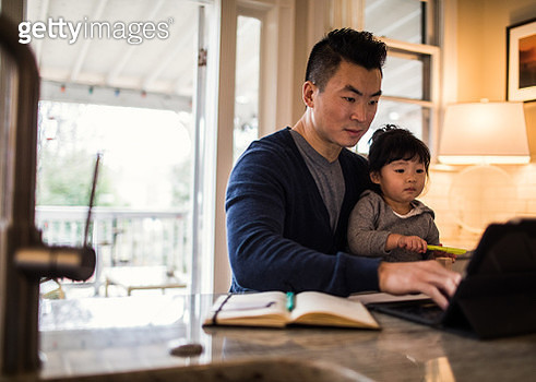 Father working in kitchen with daughter - gettyimageskorea