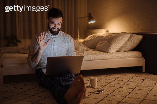 Young man making a video call on his laptop while sitting on his bedroom floor at home at night - gettyimageskorea