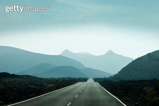 Empty road leading towards mountains in Lanzarote, Canary Islands, Spain - gettyimageskorea