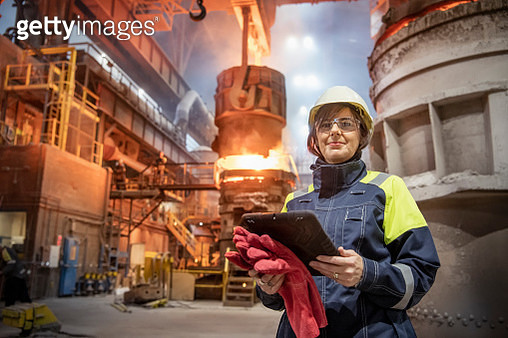 Portrait of female steelworker during steel pour in steelworks - gettyimageskorea