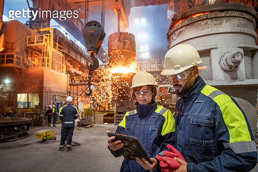 Male and female steelworkers using digital tablet during steel pour in steelworks - gettyimageskorea