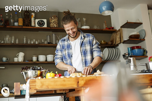 Young man preparing food at home, slicing bread - gettyimageskorea