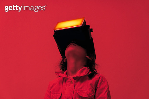 A child wearing virtual reality glasses surrounded with red colored light looking up. - gettyimageskorea