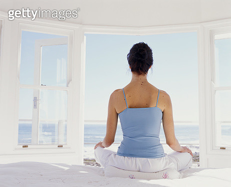 Young woman meditating on bed facing open window, rear view - gettyimageskorea