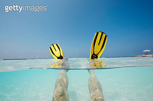 Maldives, mans feet with flippers in shallow water - gettyimageskorea