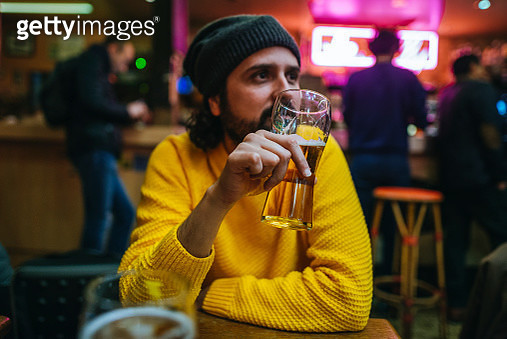 Man with glass of beer in a pub - gettyimageskorea