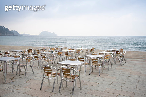 Empty chairs and tables in front of the Cantabrian sea, Zarautz, Basque Country - gettyimageskorea