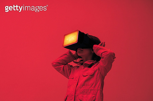 A child wearing virtual reality glasses expressing feelings by covering her ears, surrounded with red colored light. - gettyimageskorea