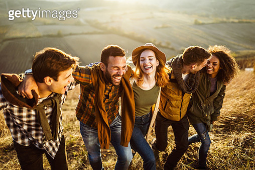 Group of cheerful friends having fun while walking embraced on the hill. - gettyimageskorea