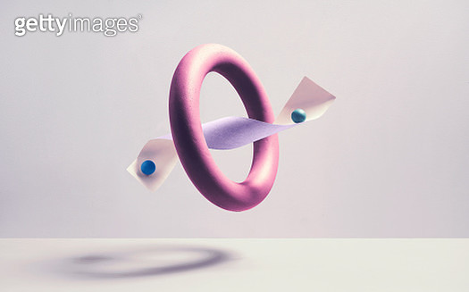 A conceptual image where marbles symbolizes individuals balancing on each side of a paper threw a spherical ring. - gettyimageskorea