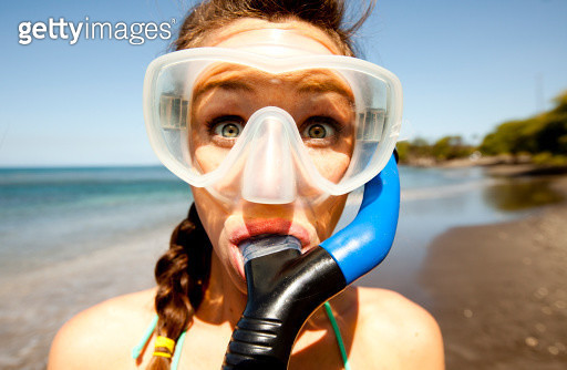 A woman with wide eyes wearing snorkeling gear. - gettyimageskorea