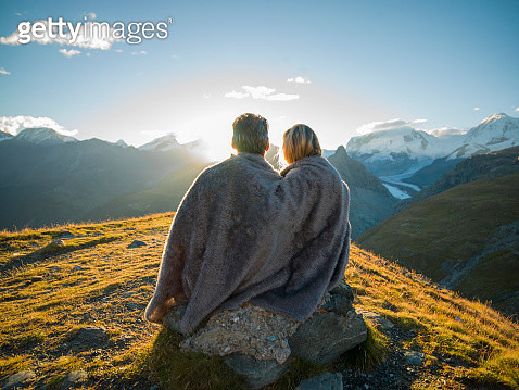 Couple huddle in blanket, watch mountain sunrise - gettyimageskorea