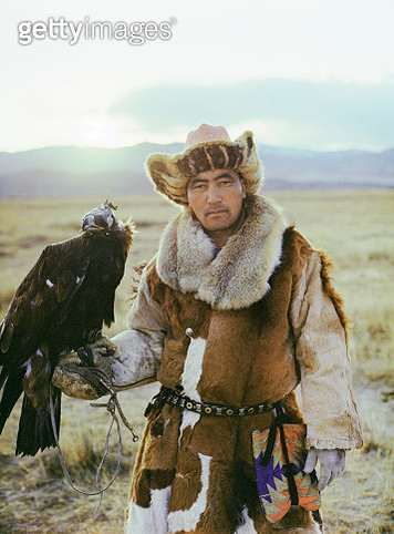 Portrait of eagle hunter standing in steppe in Mongolia - gettyimageskorea