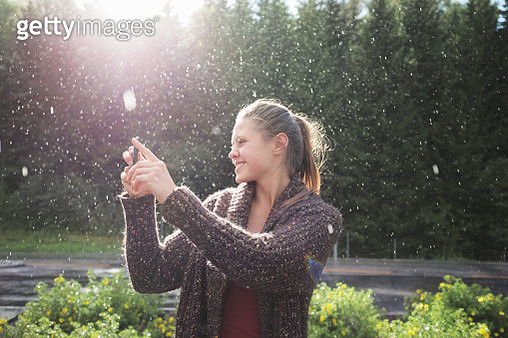 Woman taking picture of rain and sun, smiling - gettyimageskorea