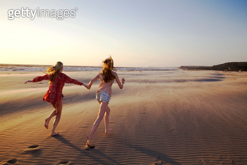 Maother and daughter running on empty beach - gettyimageskorea