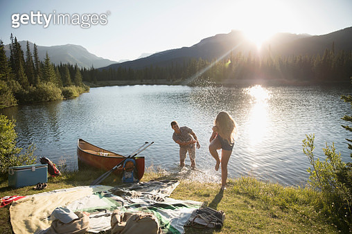 Playful young couple splashing water at sunny summer lake - gettyimageskorea