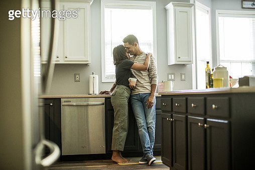 Husband and wife talking in kitchen - gettyimageskorea