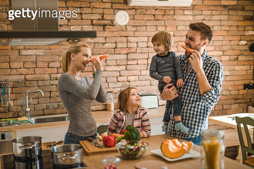 Playful family having fun with carrots in the kitchen. - gettyimageskorea
