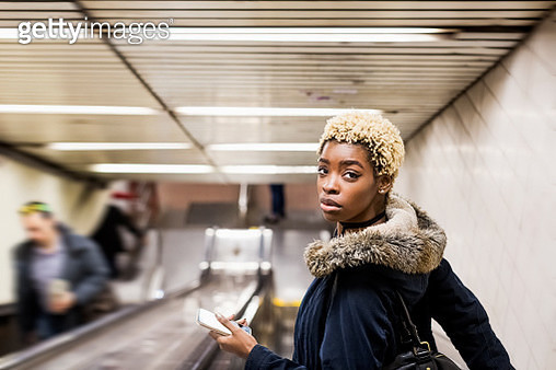 Portrait of young woman with cell phone on escaltor in underground station - gettyimageskorea
