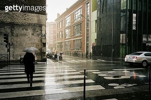 Rear View Of Woman Walking On Zebra Crossing At Wet Street By Buildings During Monsoon - gettyimageskorea