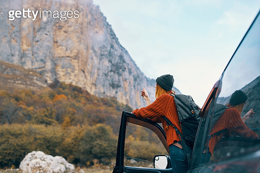 Woman got out of the car and looks at the mountains - gettyimageskorea