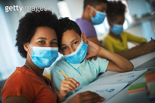 Closeup side view of young african american couple home schooling their children. They are in the living room, all wearing face masks during coronavirus quarantine. Mother and son are looking at the camera. - gettyimageskorea