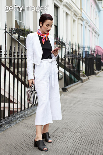 Woman in linen suit looking at phone in street, full length - gettyimageskorea