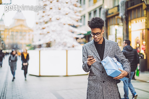 Young man is texting and holding a Christmas present - gettyimageskorea