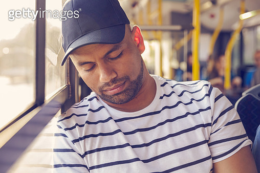 Mid adult man napping while traveling in bus. Male passenger is commuting by public transport. - gettyimageskorea