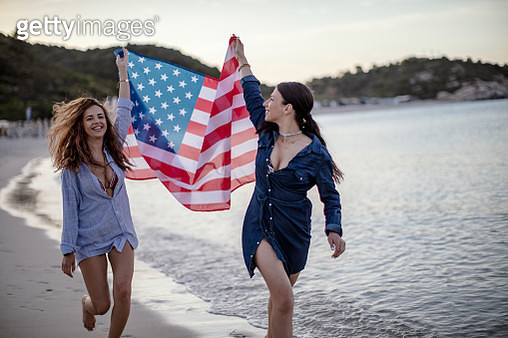 Young Women Wrapped in American Flag walking at the  Beach - gettyimageskorea