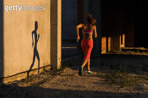 Back view of sportswoman jogging in an abandoned warehouse. - gettyimageskorea
