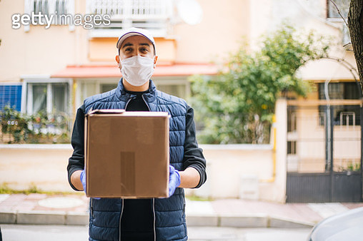 Young happy delivery man with protective mask looking at camera - gettyimageskorea