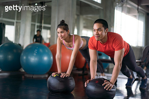 doing stretching exercises on fitness ball in gym. - gettyimageskorea