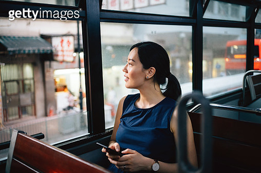 Beautiful young Asian lady with smartphone enjoying city scene through window while riding on public transportation in city - gettyimageskorea