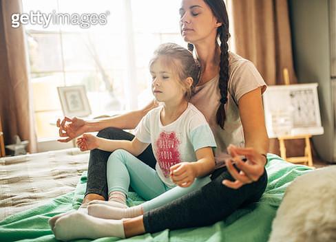 Mother and daughter practicing  in bedroom - gettyimageskorea