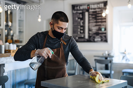 Young man barista with face mask and gloves standing in coffee shop, disinfecting tables. - gettyimageskorea